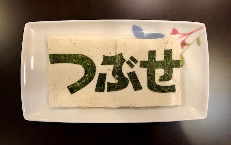豆腐の上に「つぶせ」と刻んだ海苔