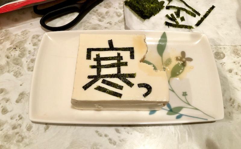 豆腐の上に「寒っ」と刻んだ海苔